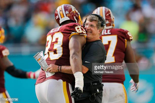 Interim head coach Bill Callahan of the Washington Redskins hugs Jonathan Allen after a stopping a two-point conversion attempt against the Miami...