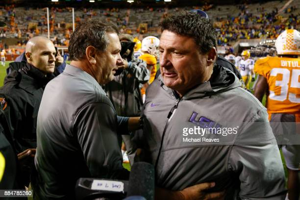 Interim head coach Brady Hoke of the Tennessee Volunteers shakes hands with head coach Ed Orgeron of the LSU Tigers at Neyland Stadium on November 18...
