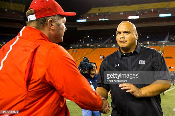 Interim head coach Chris Naeole of the Hawaii Warriors and head coach Tim Deruyter of the Fresno State Bulldogs greet each other at the conclusion of...