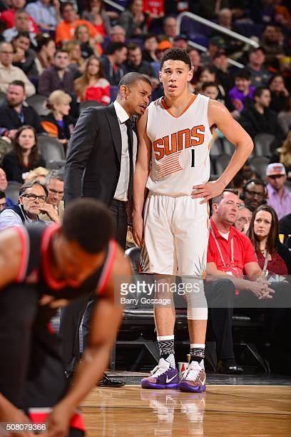 Interim head coach Earl Watson of the Phoenix Suns talks with Devin Booker of the Phoenix Suns during the game against the Toronto Raptors on...