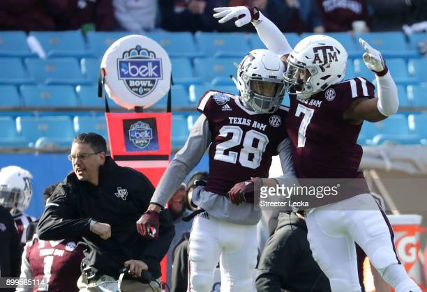 Interim head coach Jeff Banks reacts with players Travon Fuller and Buddy Johnson of the Texas AM Aggies after a play against the Wake Forest Demon...