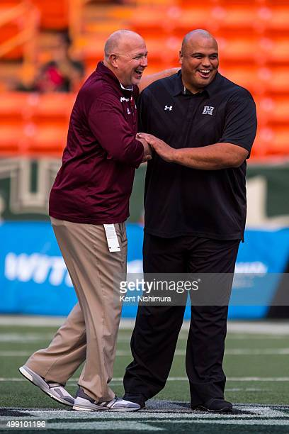 Interim head coach John Mumford of the Louisiana Monroe Warhawks and interim head coach Chris Naeole of the Hawaii Warriors talk with each other...