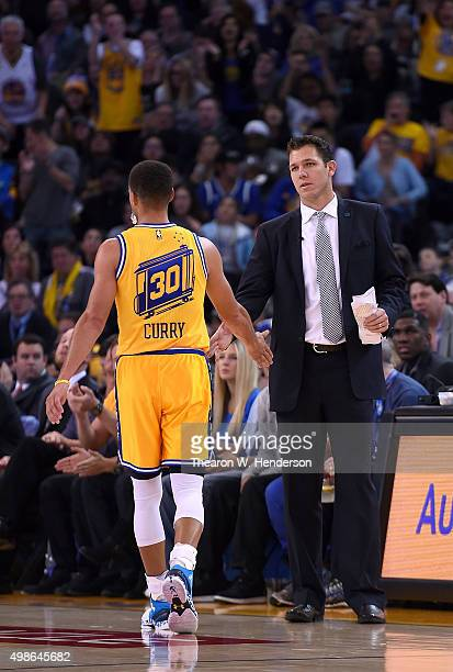 Interim head coach Luke Walton of the Golden State Warriors congratulates Stephen Curry after taking him out of the game against the Los Angeles...