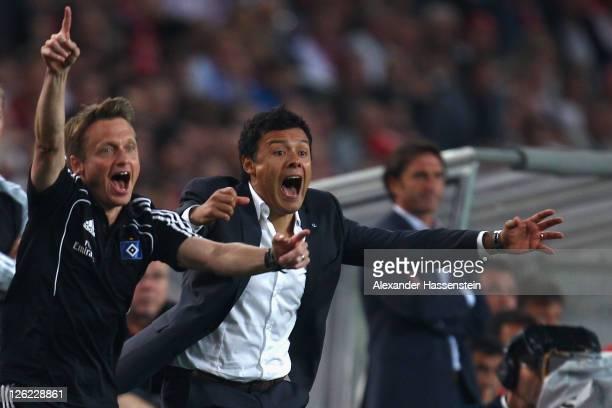 Interim head coach Rodolfo Cardoso of Hamburg celebrates his team first goal with assistent coach Frank Heinemann during the Bundesliga match between...