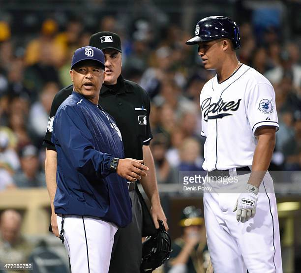 Interim manager Dave Roberts of the San Diego Padres argues a call with home plate umpire Mike DiMuro as Will Venable looks on during the third...