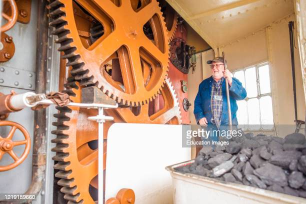 Interior cogs and mechanisms of the historic Fairbairn steam crane in the Floating Harbor section of Bristol Docks Avon England UK