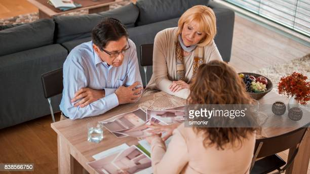 interior designer discussing with couple - interior design foto e immagini stock