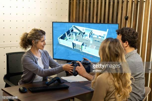 designer de interiores falando com um casal sobre seu projeto habitacional e usando tecnologia 3d - council flat - fotografias e filmes do acervo