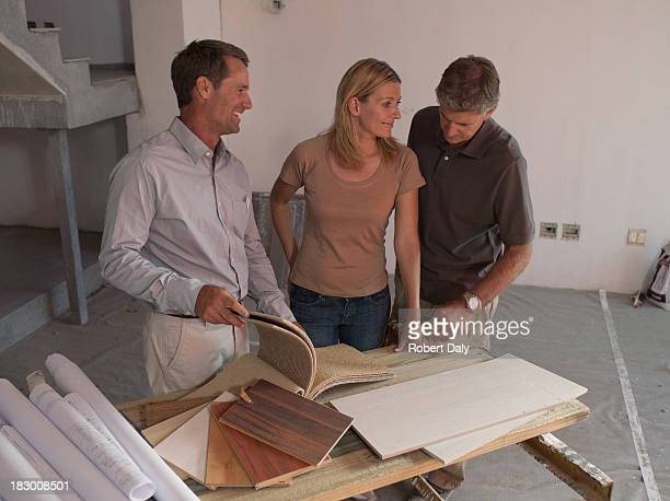 Interior designer talking with couple in new home