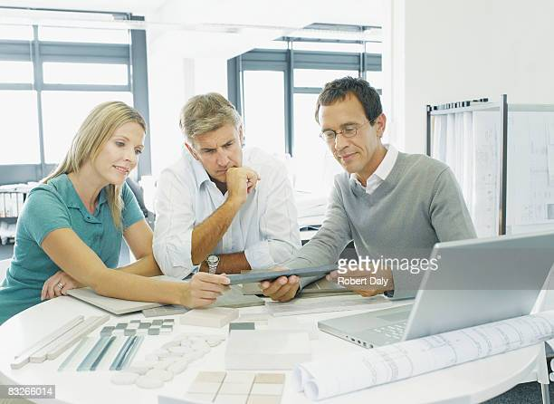 Interior designer talking with couple in showroom