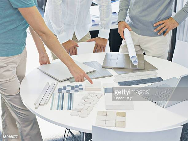 interior designer talking with couple in showroom - real estate developer stock pictures, royalty-free photos & images