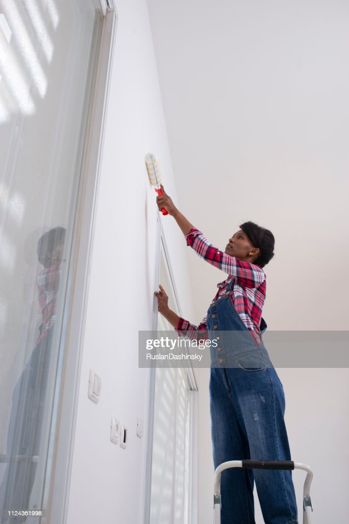 Interior house painting. Woman painting living room wall with paint roller. : Stock Photo