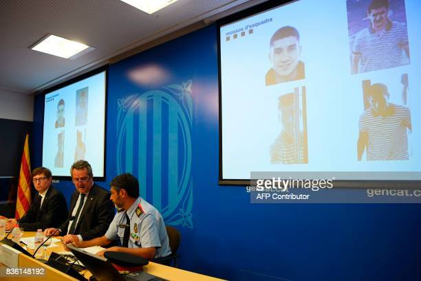 TOPSHOT Interior Minister for the Catalan government Joaquim Forn speaks past Josep Lluis Trapero chief of the Catalan regional police 'Mossos...