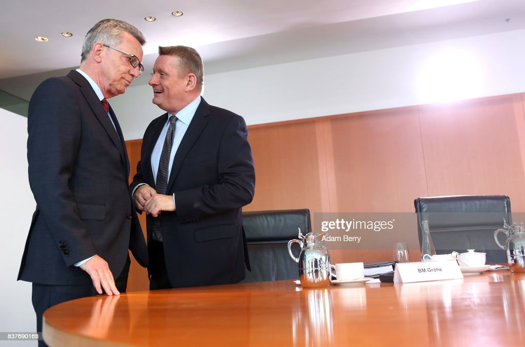 Interior Minister Thomas de Maiziere (CDU, L) speaks to Health Minister Hermann Groehe (CDU) as they arrive for the weekly German federal Cabinet meeting on August 23, 2017 in Berlin, Germany. High on the meeting's agenda was discussion of government spending.