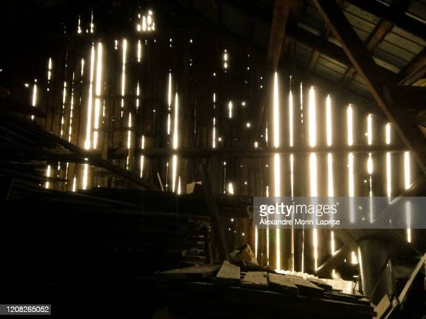 interior of a barn slightly illuminated by the sun entreing holes between the wooden planks in quebec, quebec / canada - 打ち捨てられた ストックフォトと画像