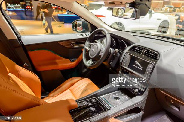 Interior of a black Jaguar F-Pace crossover SUV fitted with light leather seats, aluminium details and a large information display on the dashboard...