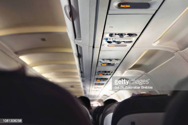 Interior of a commercial airplane, focus on the sign of the seats numbered from d to f.