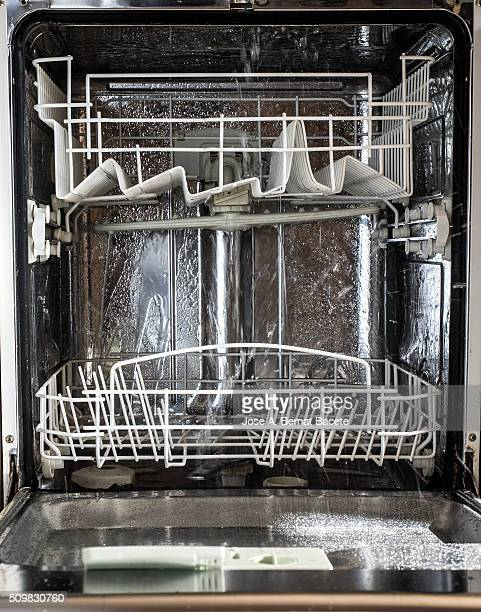 Interior of a Dishwasher opened in functioning throwing water jets