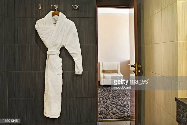 interior of a hotel room with a white dressing gown hanging up and the door open with a view through to the next room - バスローブ ストックフォトと画像