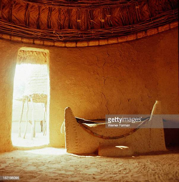 Interior of a house Both the walls and the bed are made of dried mud Outside the doorway is a grain store raised to protect the crop from animals...