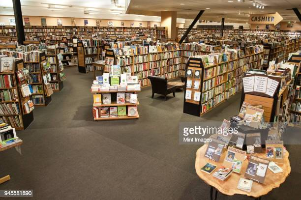 interior of a large bookstore showing multiple racks of books. - book store stock photos and pictures