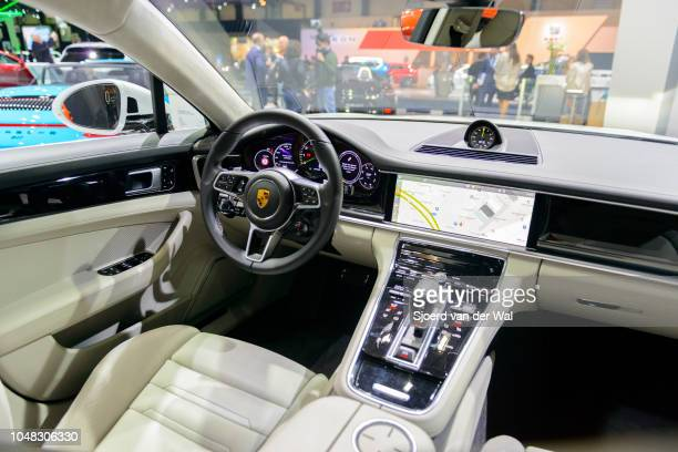 Interior of a Porsche Panamera 4 ehybrid luxury 4 door saloon performance car fitted with light leather seats and a large LED display on the...