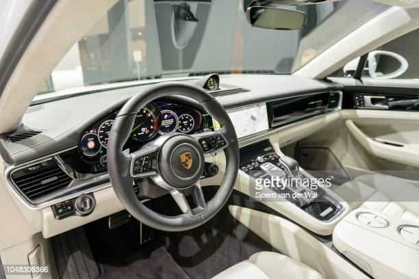 Interior of a Porsche Panamera 4 e-hybrid luxury 4 door saloon performance car fitted with light leather seats and a large LED display on the...