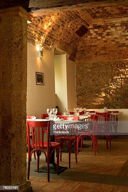 Interior of a quaint Italian restaurant with brick arch decor adn red chairs.