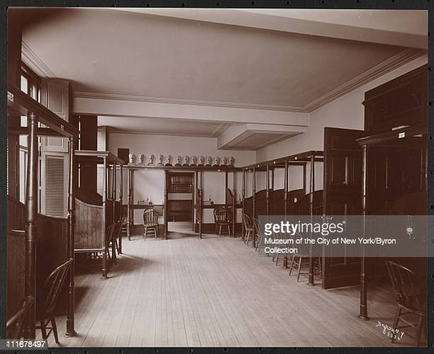 Interior of a room with examination booths along walls at the Vanderbilt Clinic at 59th Street and Amsterdam Avenue New York New York late 1890s