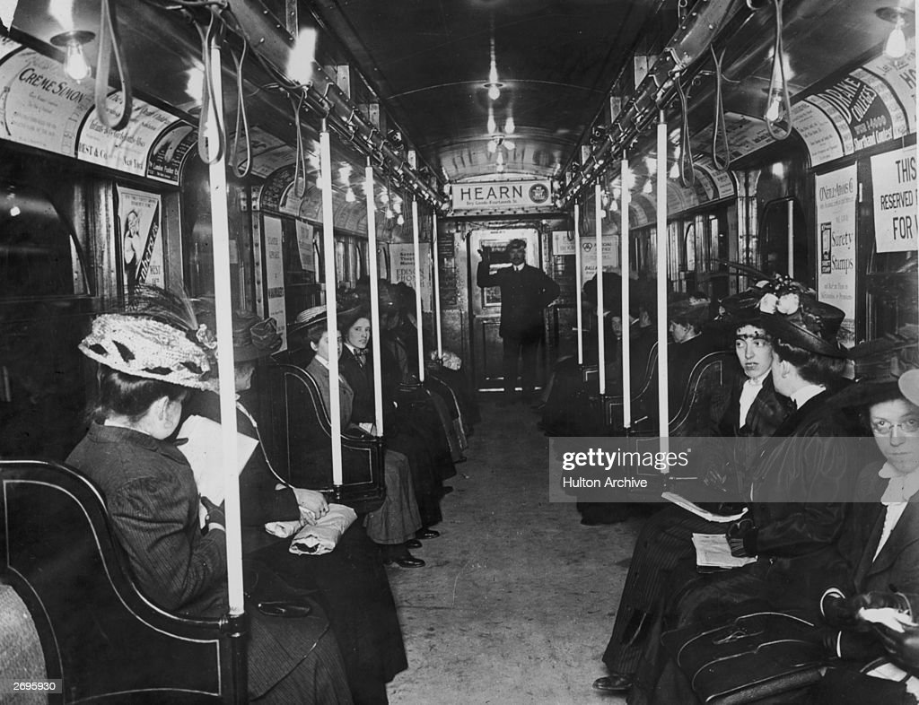 Interior of a subway car with female passengers and a uniformed male conductor.