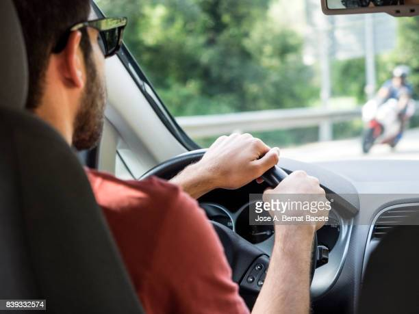 Interior of a vehicle circulating along a highway for a young adult with beard and sunglasses in Catalonia, Spain