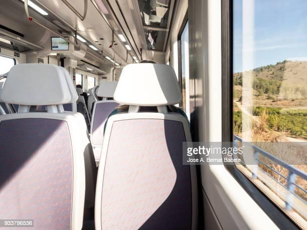 Interior of almost  empty  train in movement crossing the field.