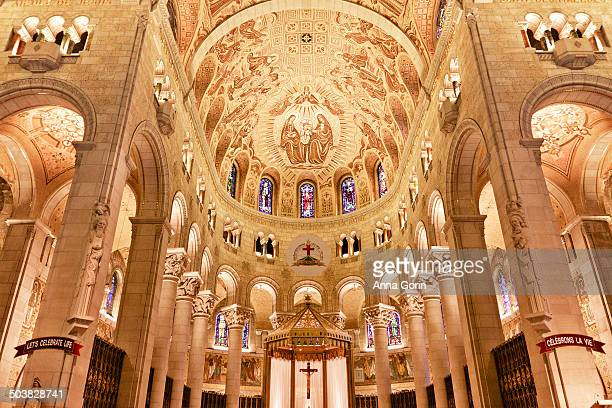 Interior of Basilica of Sainte-Anne-de-Beaupré in Quebec, Canada, looking toward High Altar and ceiling covered with stained glass and mosaics. The...