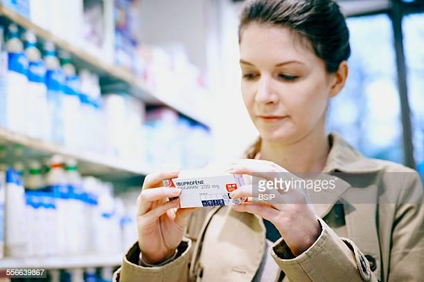 Interior of Chemists Shop Woman holding ibuprofen drug