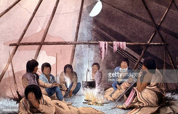 Interior of Cree Indian tent 1823 Man smoking Papoose in 'cradle' Cooking pot suspended over fire Coloured lithograp from John Franklin Narrative of...