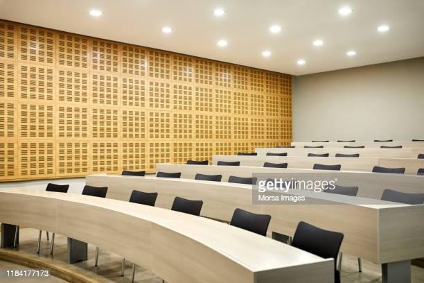 interior of empty illuminated lecture hall - universidade imagens e fotografias de stock