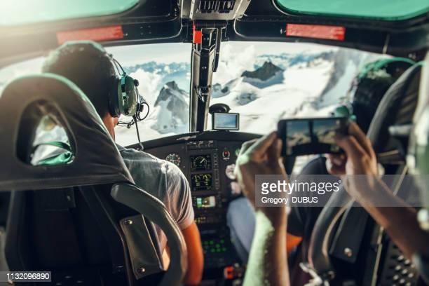 interior de cabina de helicóptero con piloto irreconocible y turista descentrado tomando fotos del vuelo sobre el macizo del mont blanc - haute savoie fotografías e imágenes de stock