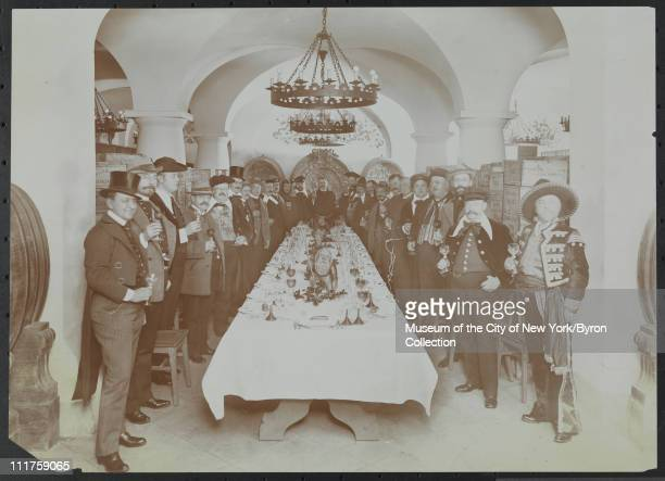 Interior of men in costume at a dinner in the rathskellar/wine cellar at the Hotel Astor Broadway and 45th Street New York New York mid 1900s