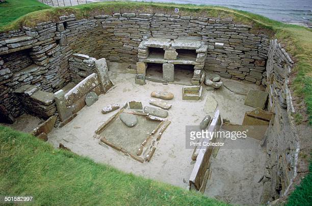 Interior of Neolithic Hut at Skara Brae Neolithic settlement Orkney circa 1960 Stone 'furniture' can be seen The hearth is in the centre and there...