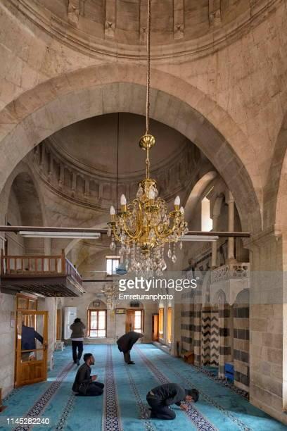 interior of rizvaniye mosque with praying people near balıklıgöl,şanlırfa . - emreturanphoto stock pictures, royalty-free photos & images