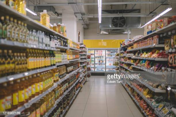 interior of supermarket full of grocery items in rows with shelf displayed - market retail space stock pictures, royalty-free photos & images