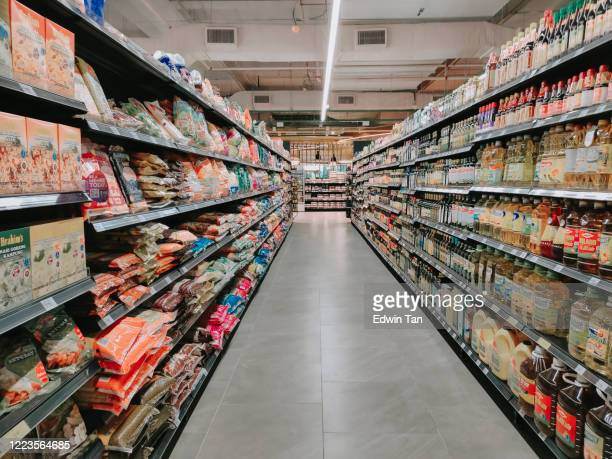 interior of supermarket full of grocery items in rows with shelf displayed - aisle stock pictures, royalty-free photos & images