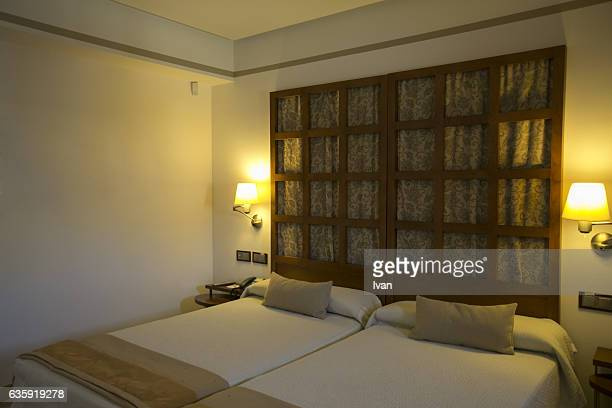Interior of the Beige and White Bedroom with Double Bed, Big Window and Yellow (Amber) Light