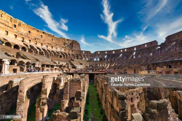 interior of the colosseum of rome on foot of sand with a blue and cloudy sky - gladiator fotografías e imágenes de stock