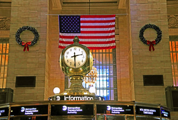 Interior of the Grand Central Terminal during Christmas holiday showing clock above information booth and American flag in background
