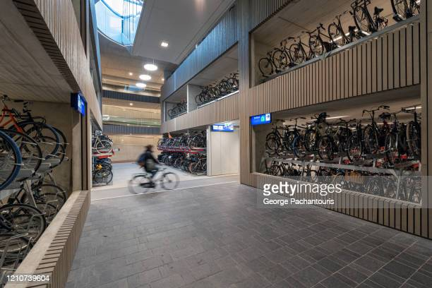 interior of the world's largest bicycle parking garage in utrecht, holland - utrecht stock pictures, royalty-free photos & images