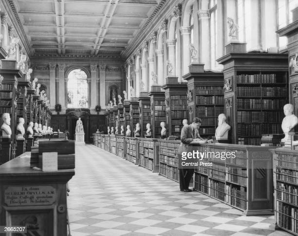 Interior of Trinity College Library Cambridge designed by Sir Christopher Wren It houses over 50000 volumes and the busts are of former fellows and...