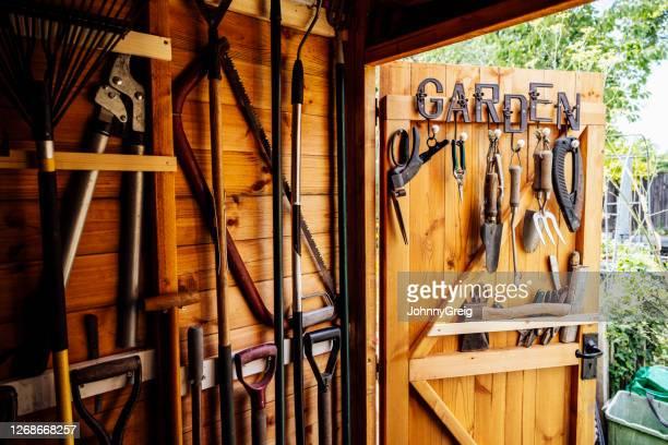 inneneinrichtung eines holzgartenschuppens mit ordentlich angeordneten werkzeugen - lagerhaltung stock-fotos und bilder