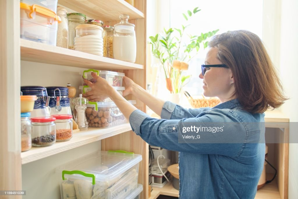 Interior of wooden pantry with products for cooking. Adult woman taking kitchenware and food from the shelves : Stock Photo