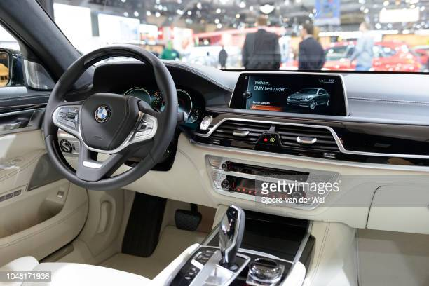Interior on a BMW 7 series luxury limousine car fitted with leather seats wood details and a large information display on the dahsboard on display at...